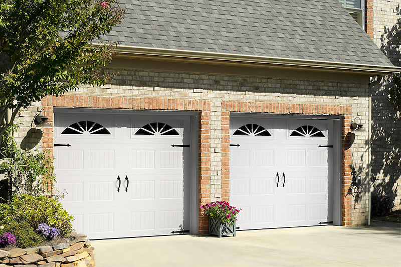 Two white garage doors on a brick residential building