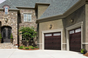 two brown wooden garage doors on a nice southwestern residential home
